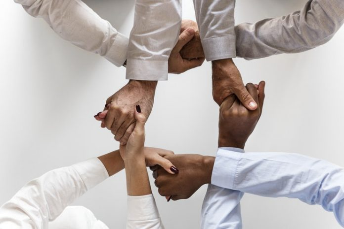 A diverse team holds hands, representing diversity and workplace culture
