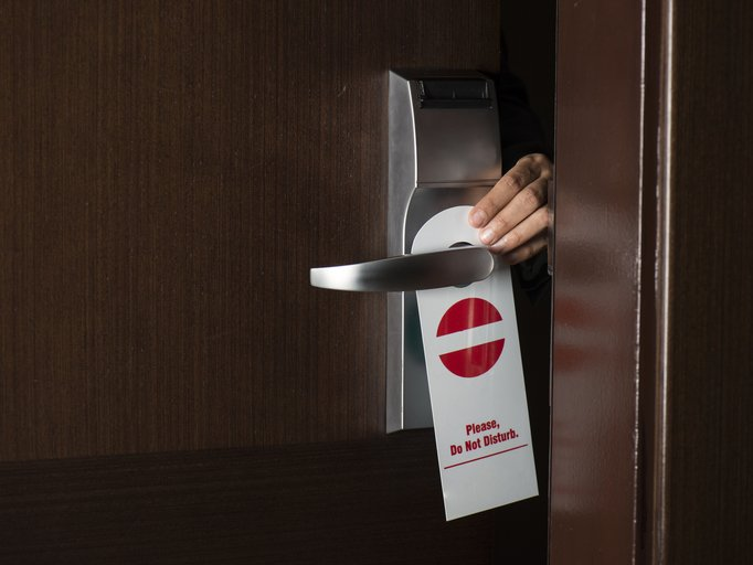 Hand hanging 'Do Not Disturb' sign on hotel door