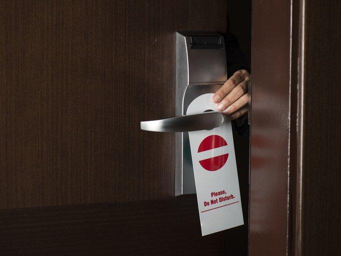 Hand hanging 'Do Not Disturb' sign on hotel door