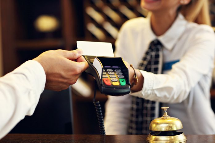Man pays with a credit card at the front desk of a hotel