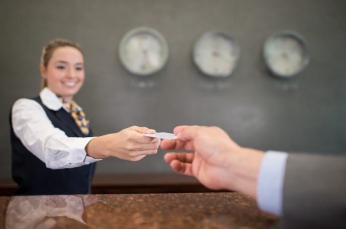 Woman working at a hotel handing a loyalty card or card key at the front desk