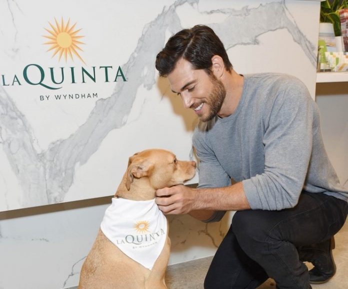 Veterinarian Dr. Evan Antin and therapy dog Boon 'Take A Paws' at a La Quinta by Wyndham hotel.