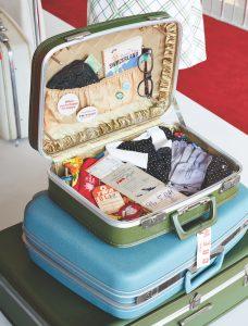 A vintage suitcase packed with retro TWA ephemera exhibited at the TWA Hotel.