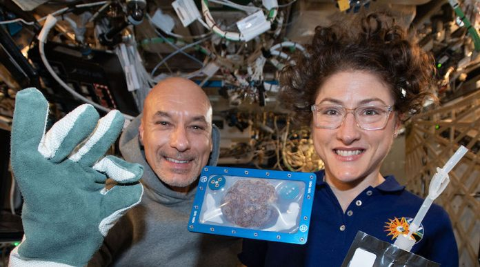 ISS Commander Luca Parmitano of the European Space Agency and NASA astronaut Christina Koch with DoubleTree cookies