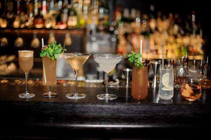 Set of classic cocktails: Dirty Martini, Sherry Cobbler, Brandy Crusta, Margarita, Cobras Fang,Tom Collins and Captain James Cook arranged on the bar counter
