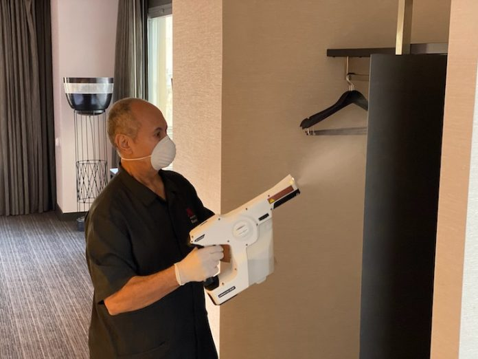 A Marriott International associate uses an electrostatic sprayer with hospital-grade disinfectant to sanitize surfaces.