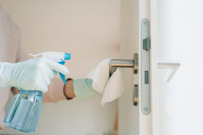 Woman in protective gloves cleaning a door handle with a disinfection spray and disposable wipes