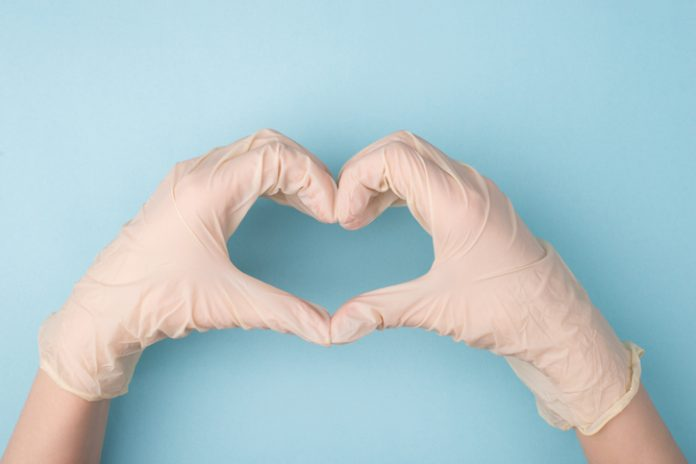 gloved hands form a heart