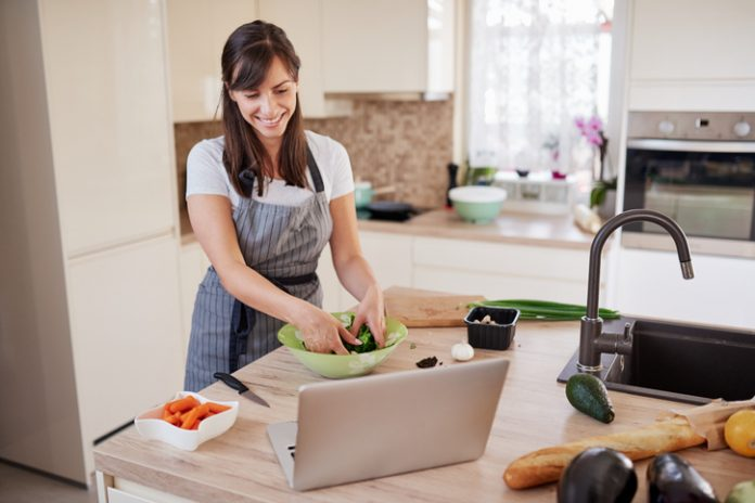 woman cooking with computer