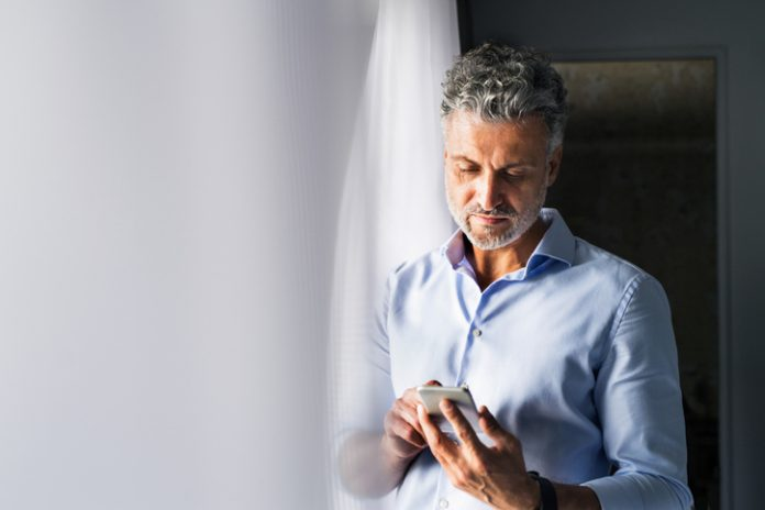 man on his smartphone in hotel guestroom