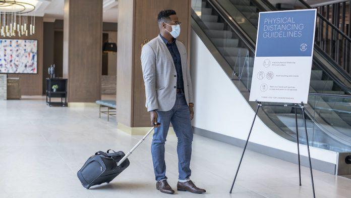 Guest in face covering arriving at Hyatt Regency Jacksonville