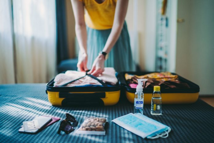 Traveler packing suitcase, including face coverings