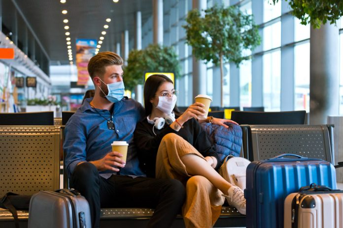 Young woman and man traveling by plane during COVID 19, wearing N95 face masks, sitting on bench with take away coffee in airport waiting area.
