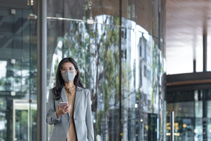 Woman wearing a face mask holding a phone