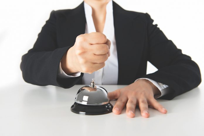 person holding a fist over a hotel front-desk bell