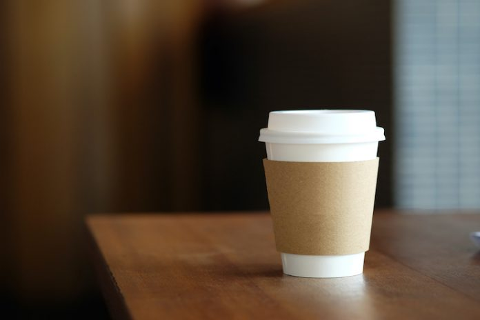 A disposable paper coffee cup sits on a wooden table