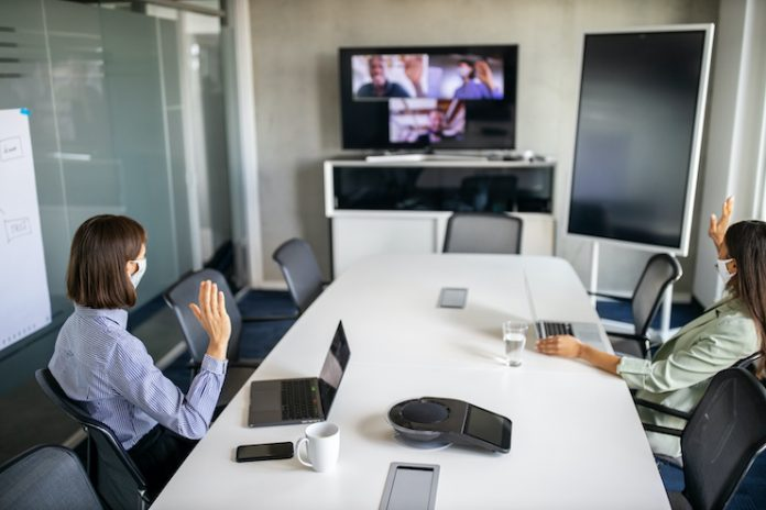 Two people sit at a conference table waving at three people attending virtually visible on a screen at a hybrid meeting