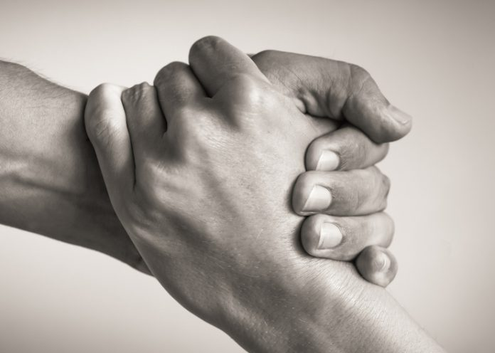 Human trafficking support concept: A hand is shown gripping another hand