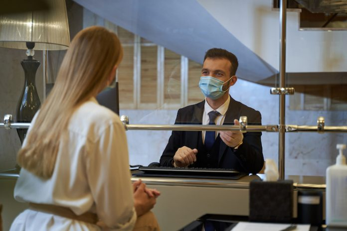 Hotel front-desk staff member checking in a guest while wearing a face mask