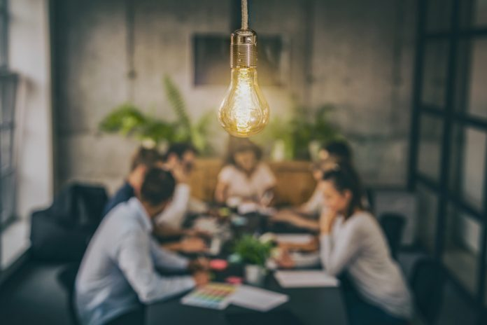 Group of people meet with lightbulb in foreground, signifying innovation